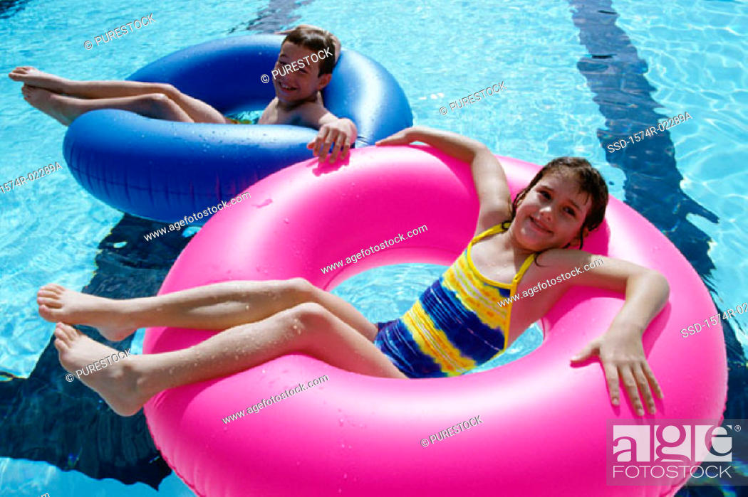 Stock Photo: High angle view of a boy and a girl lying on inflatable rings in a swimming pool.