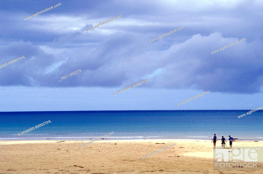 Stock Photo: Vast expanse of open beach along the southern Australian coastline with three surfies seen in the distance enjoying the freedom af the wide open spaces.