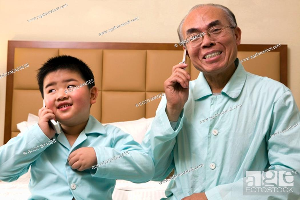 Imagen: Middle-aged man and grandson talking on cell phones in pajamas.
