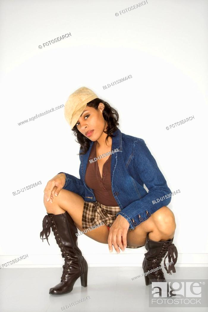Stock Photo: Woman kneeling wearing mini skirt.