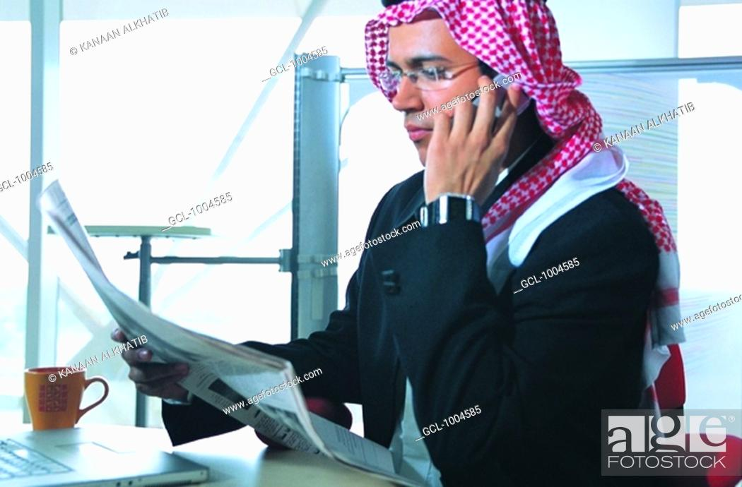 Stock Photo: Saudi Arabian businessman reading newspaper in office.