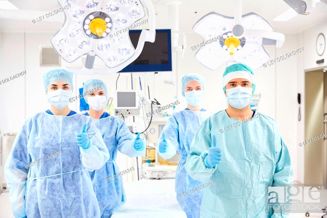 Stock Photo: surgery, medicine and people concept - group of surgeons in operating room at hospital showing thumbs up.