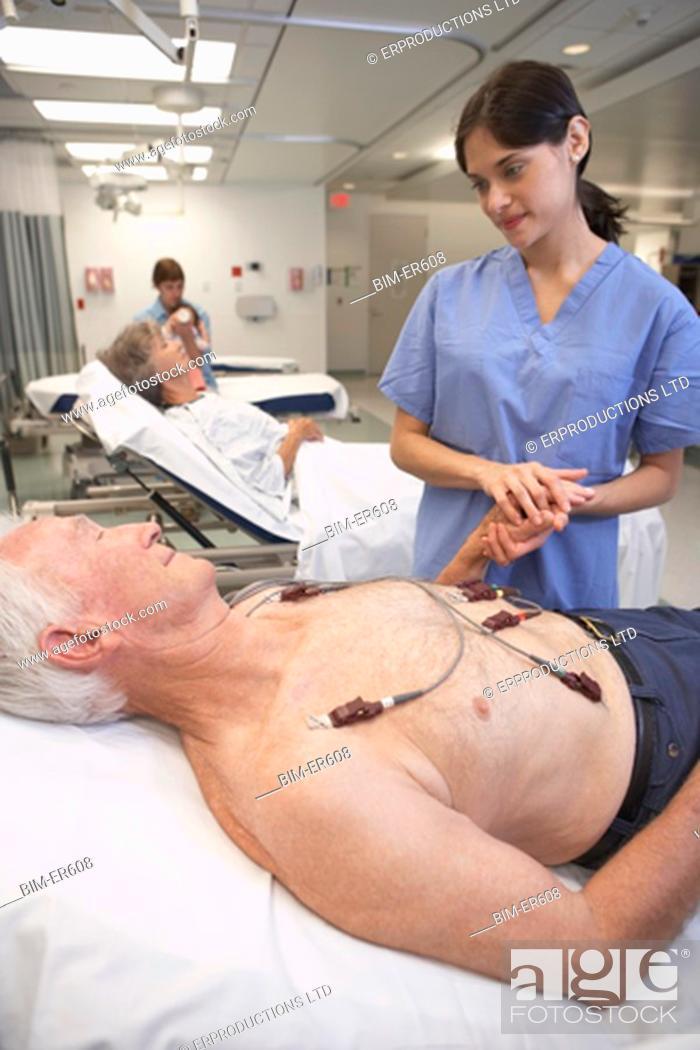 Stock Photo: Nurse holding senior male patientÆs hand in hospital.