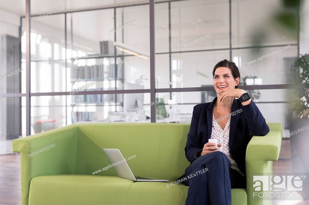 Stock Photo: Businesswoman with laptop sitting on a couch and drinking coffee in the office.