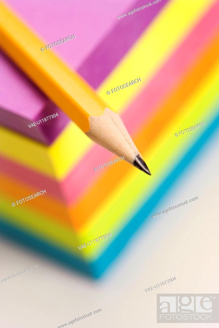 Stock Photo: Close up of sharp pencil on stack of colorful sticky notes.