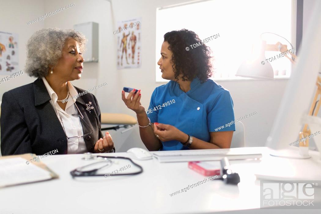 Imagen: Female doctor teaching senior patient how to use glucometer in doctors office.