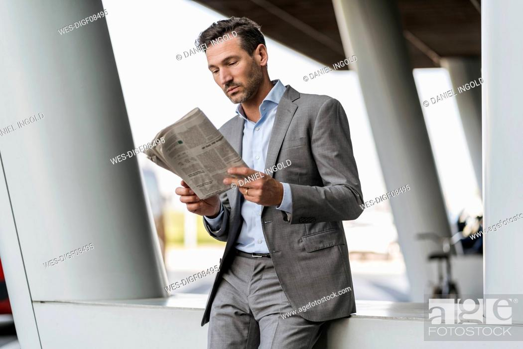 Stock Photo: Portrait of businessman reading newspaper outdoors.
