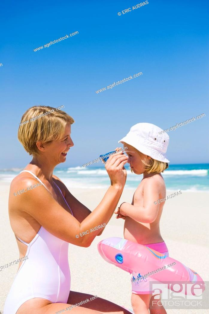 Stock Photo: Woman putting on sunglasses on her daughter's face.