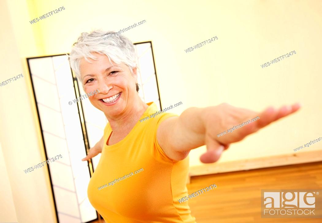 Stock Photo: Senior woman with outstretched arms, smiling, portrait.