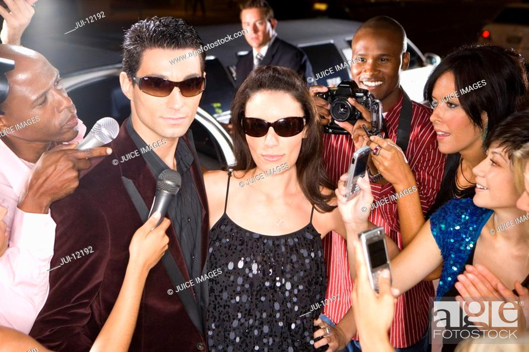Stock Photo: Young couple in sunglasses surrounded in paparazzi, close-up.
