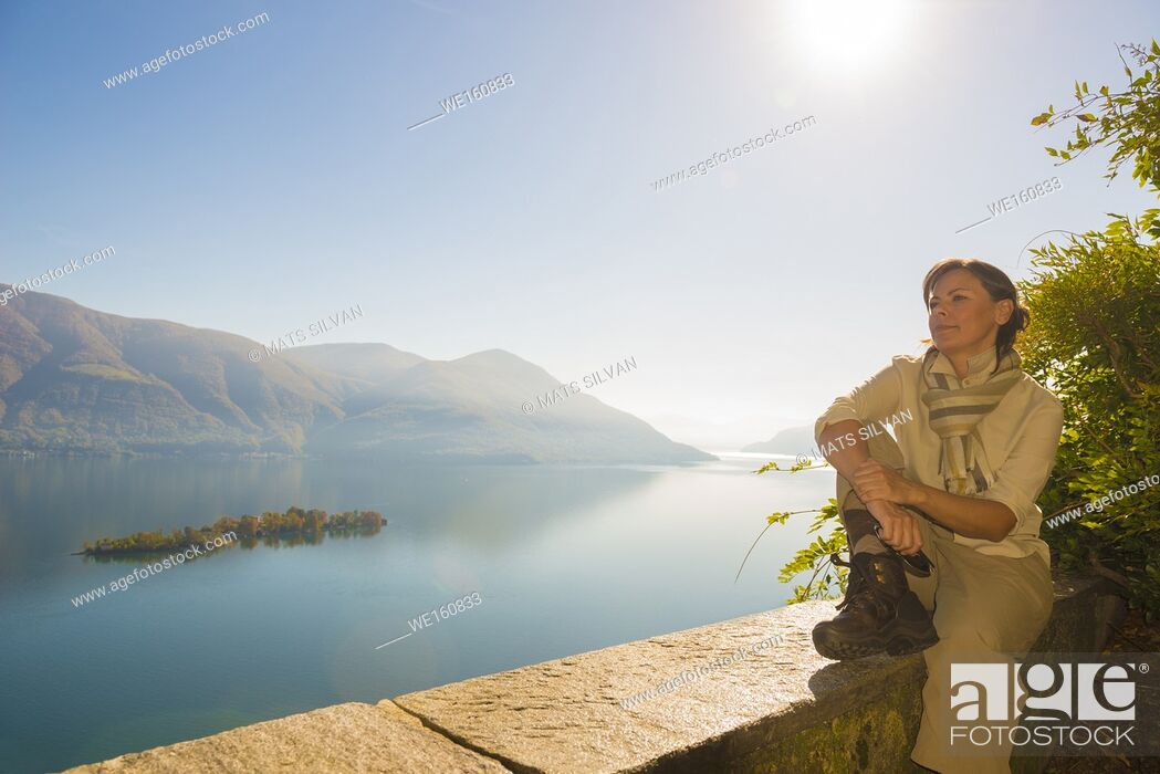 Stock Photo: Woman Relax and Enjoy the Panoramic View Over Alpine Lake Maggiore with Brissago Islands and mountain with Sunshine in Ticino, Switzerland.
