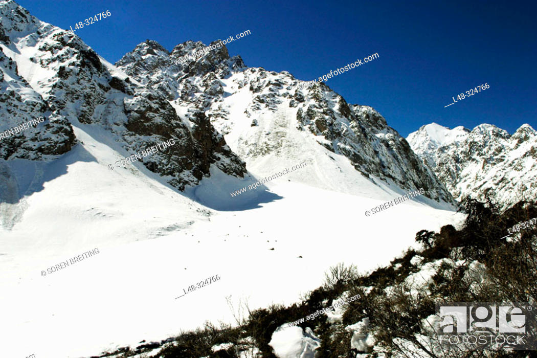 Stock Photo: Kyrgyzstan, Central Asia: Mountains and valley with snow near the capital Bishkek during early spring in april with blue sky.