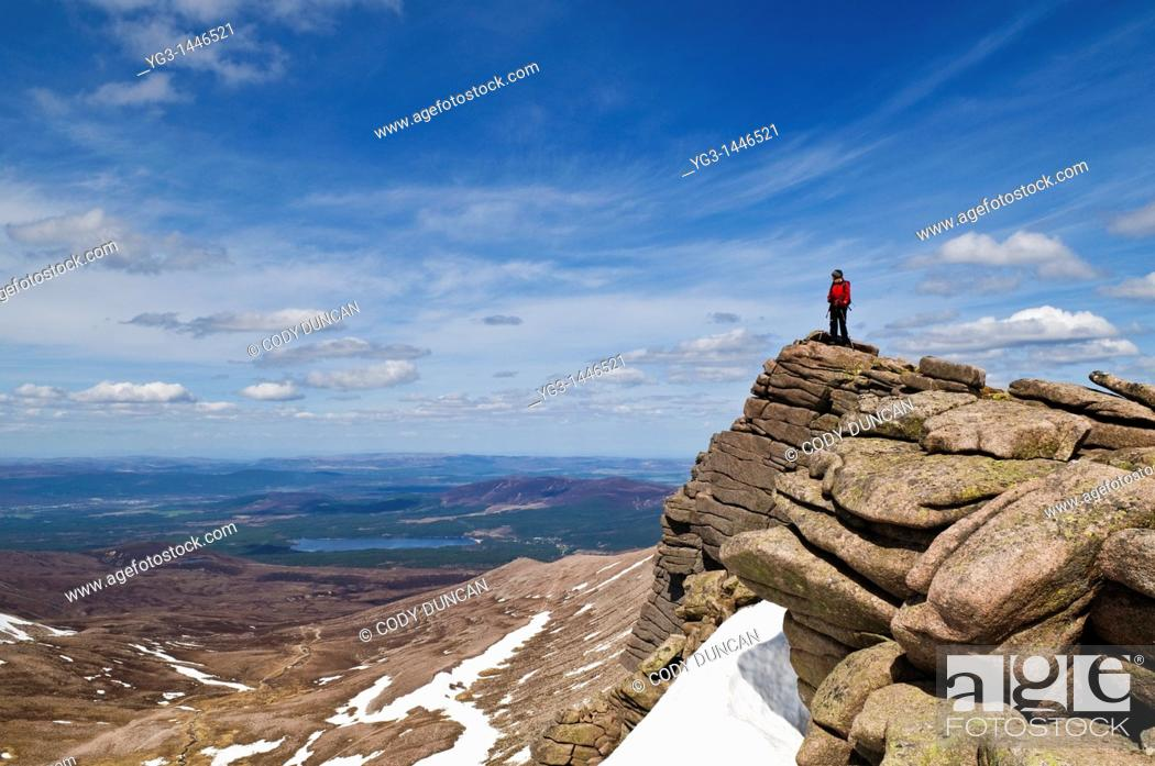 Stock Photo: Female hiker stands on rocky outlook and enjoys view, Cairngorms national park, Scotland.