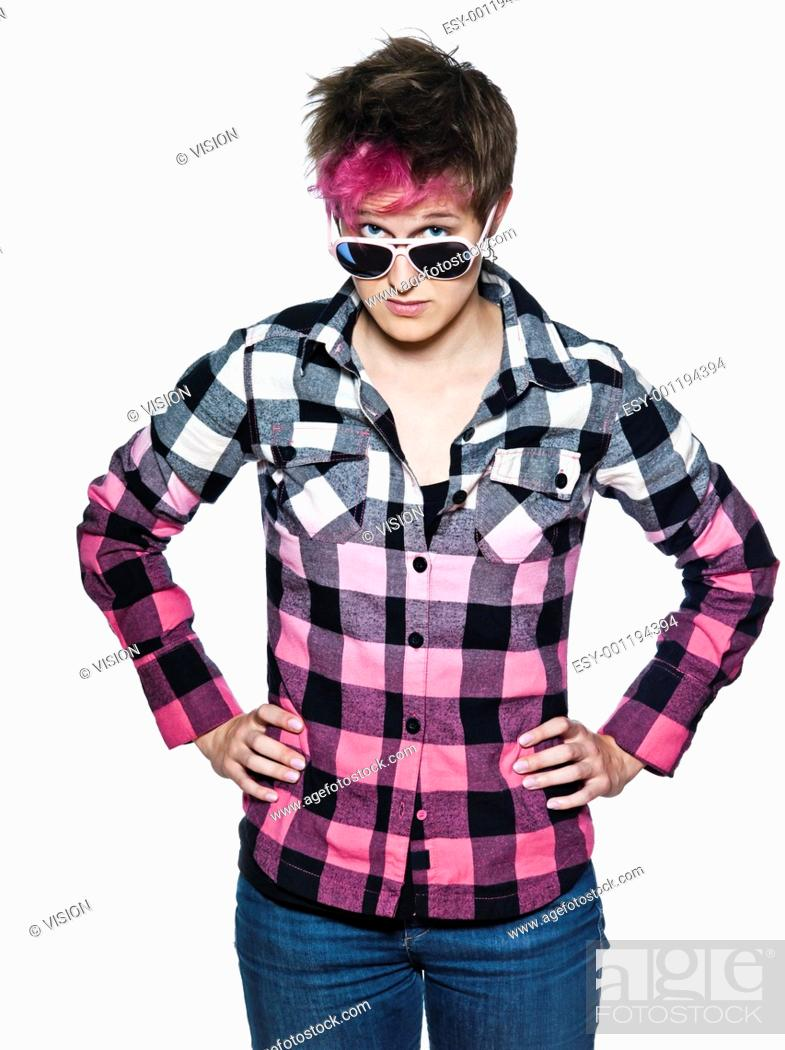 Stock Photo: Portrait of a young expressive woman peers out over her sunglasses in studio on white isolated background.