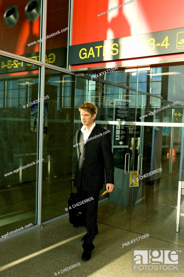 Stock Photo: Businessman walking with his luggage at an airport.