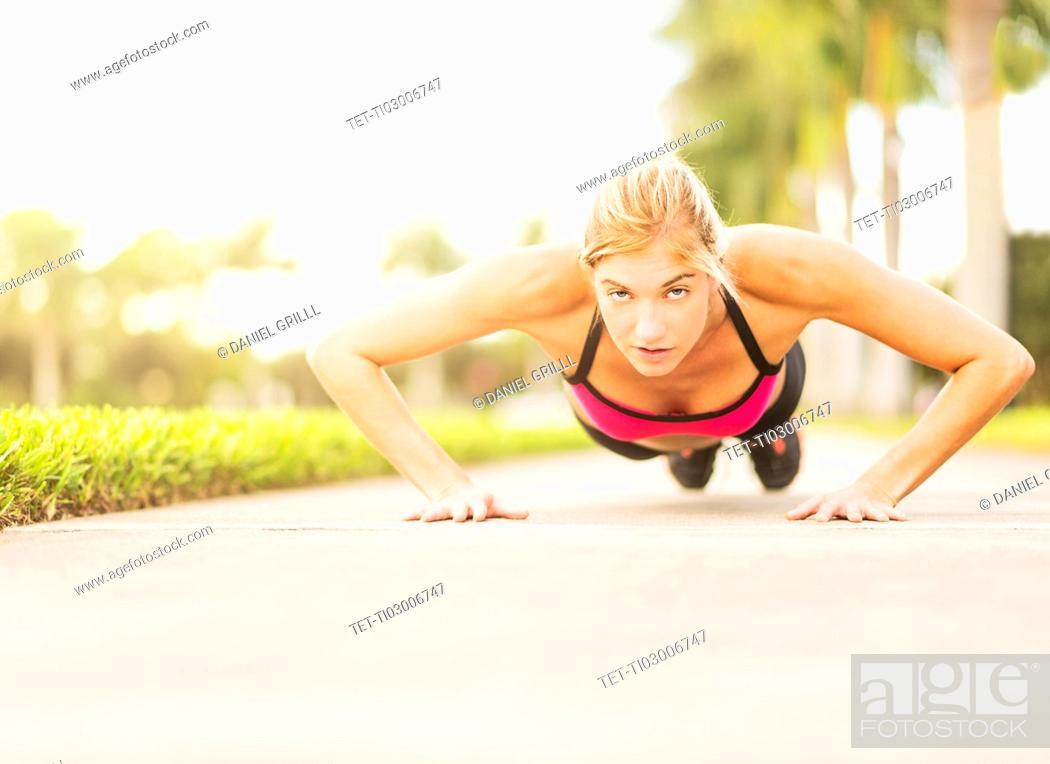 Stock Photo: Woman doing pushups outdoors.