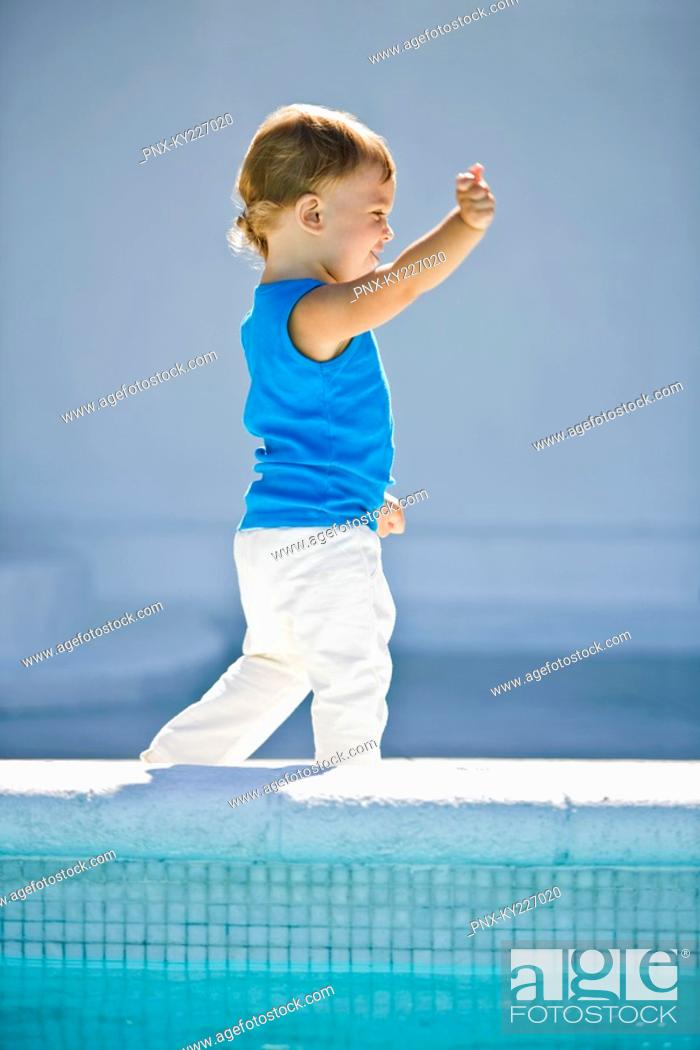 Stock Photo: Baby boy walking at the poolside.