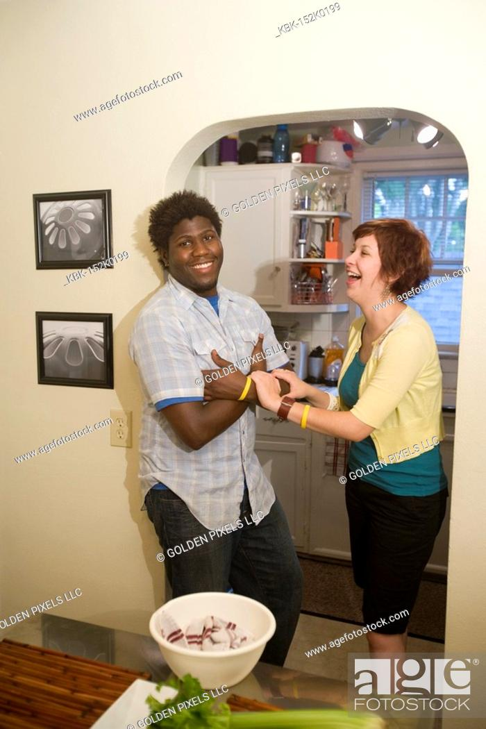Imagen: Portrait of a smiling young inter-racial couple outside their kitchen.