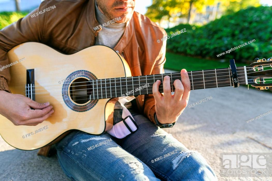 Imagen: Close-up of man playing guitar in a park.