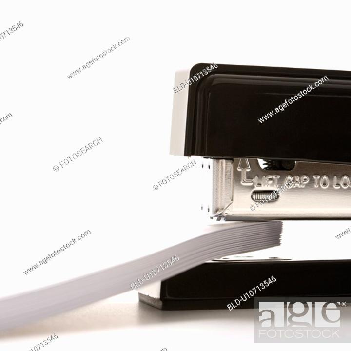 Stock Photo: Close up of black stapler on white background stapling paper.