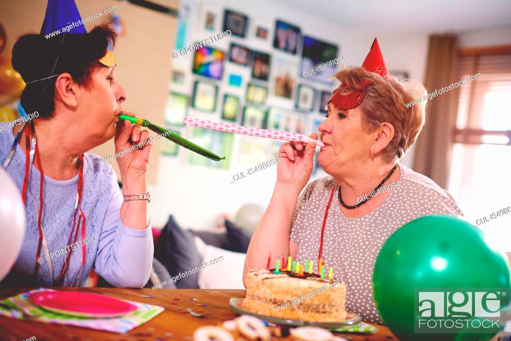 Stock Photo: Senior women blowing party favor at each other.