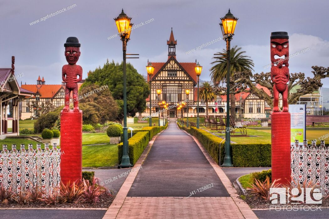 Stock Photo: Rotorua Museum entrance pathway lined by lamps and Maori wooden carved figures, dusk, Government gardens, Rotorua.