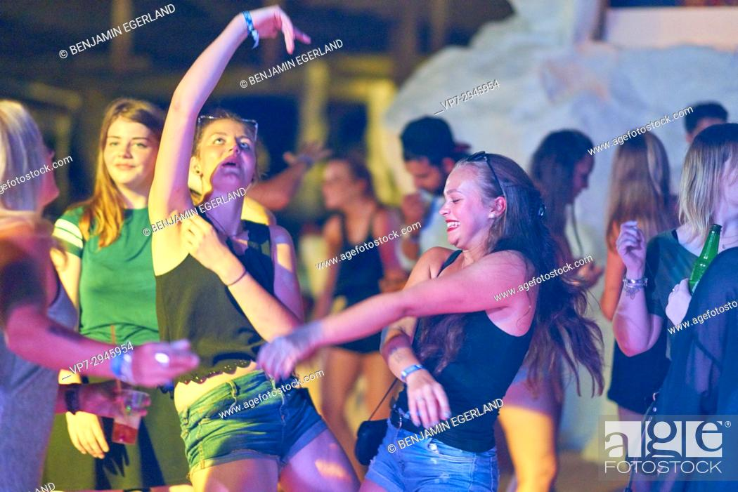 Imagen: happy girls dancing at summer party at music festival. German ethnicity. At holiday destination Hersonissos, Crete, Greece.