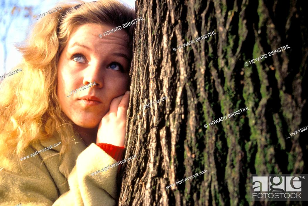 Stock Photo: close up of blond girl leaning against tree and looking into the distance.