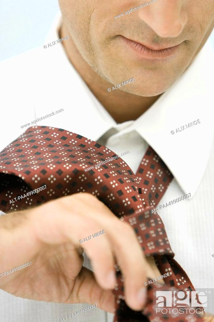 Stock Photo: Man putting on neck tie, close-up, cropped.