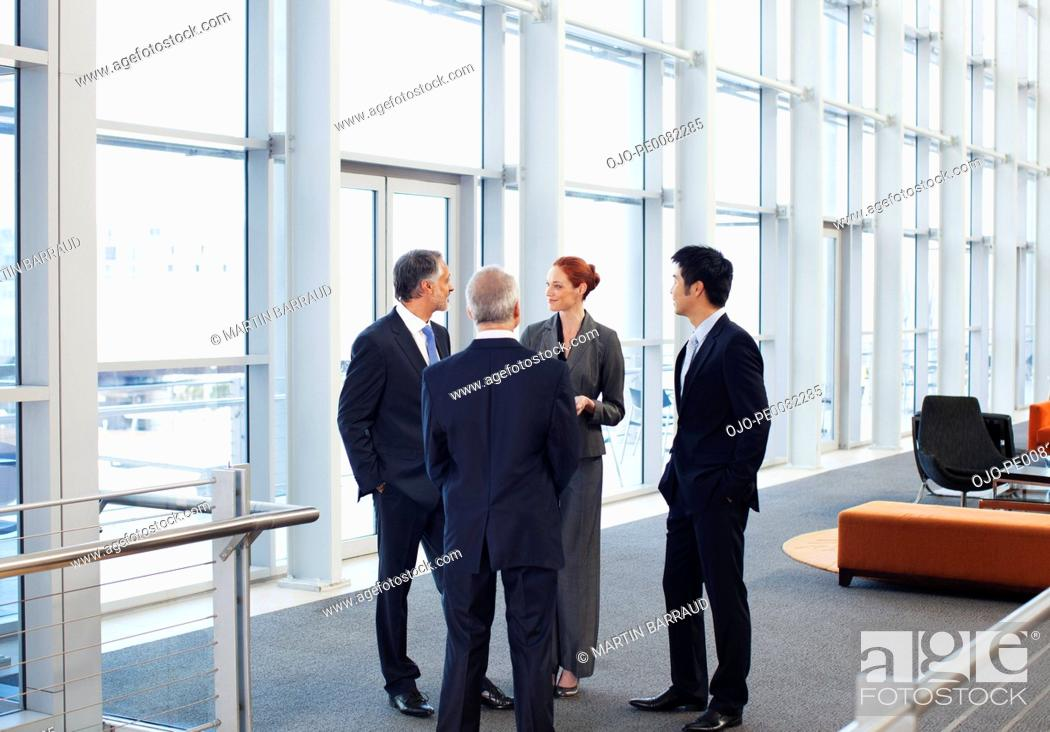 Stock Photo: Business people meeting at window in office lobby.