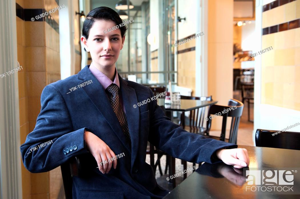 Stock Photo: Tilburg, Netherlands  Young woman, dressed up as a businessman, having lunch in a grand-cafe.