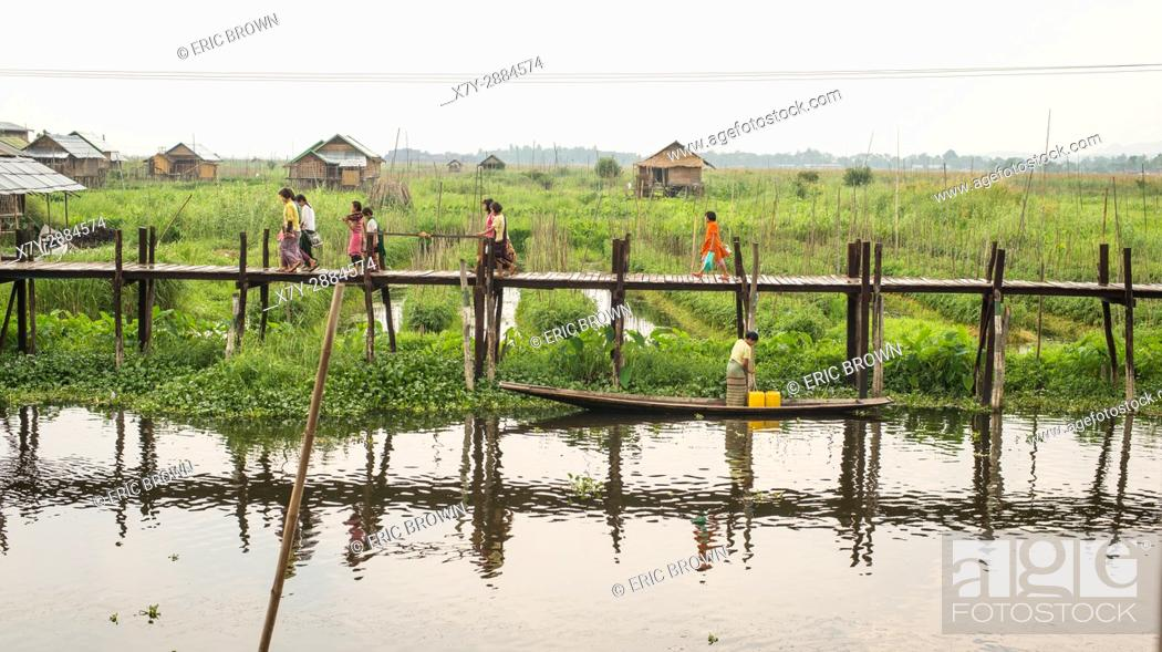Stock Photo: People walking along a dock in Inle Lake, Myanmar.