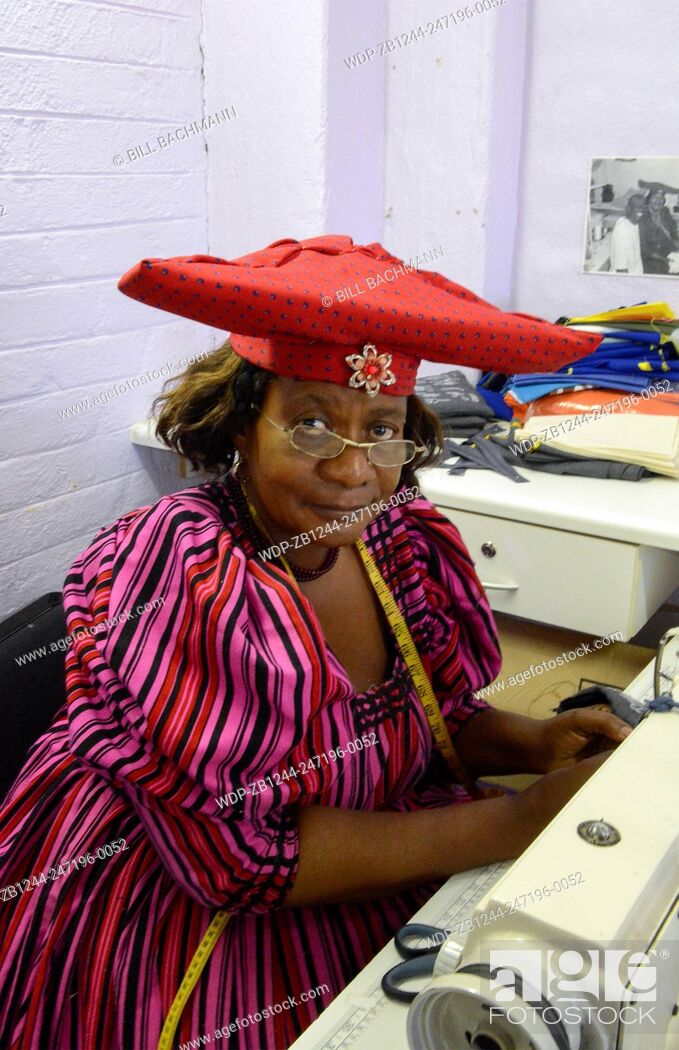 Imagen: Windhoek Namibia Africa Herero tribe woman sewing fabrics and crafts at Penduka Craft Center for sale to tourists.