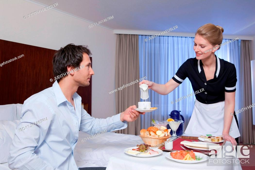 Stock Photo: room maid serving businessman in his room.