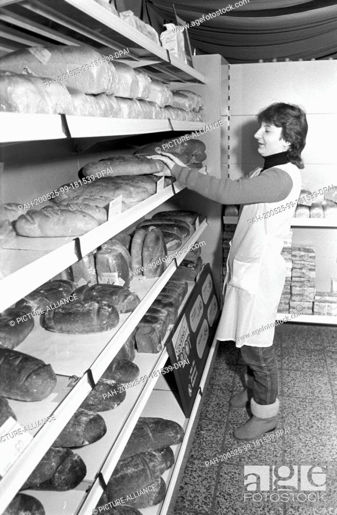 Stock Photo: 30 November 1984, Saxony, Torgau: In a department store in Torgau, a saleswoman arranges bread on the shelf in the mid-1980s.