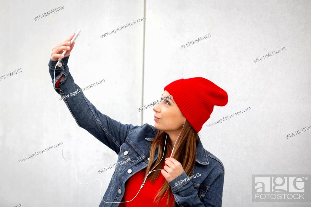 Imagen: Woman wearing red pullover and wolly hat and taking a selfie in front of a wall.