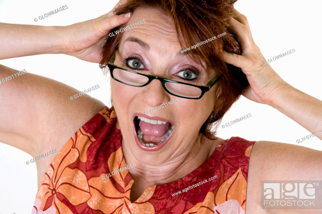 Stock Photo: Portrait of a senior woman with her hands on her head.