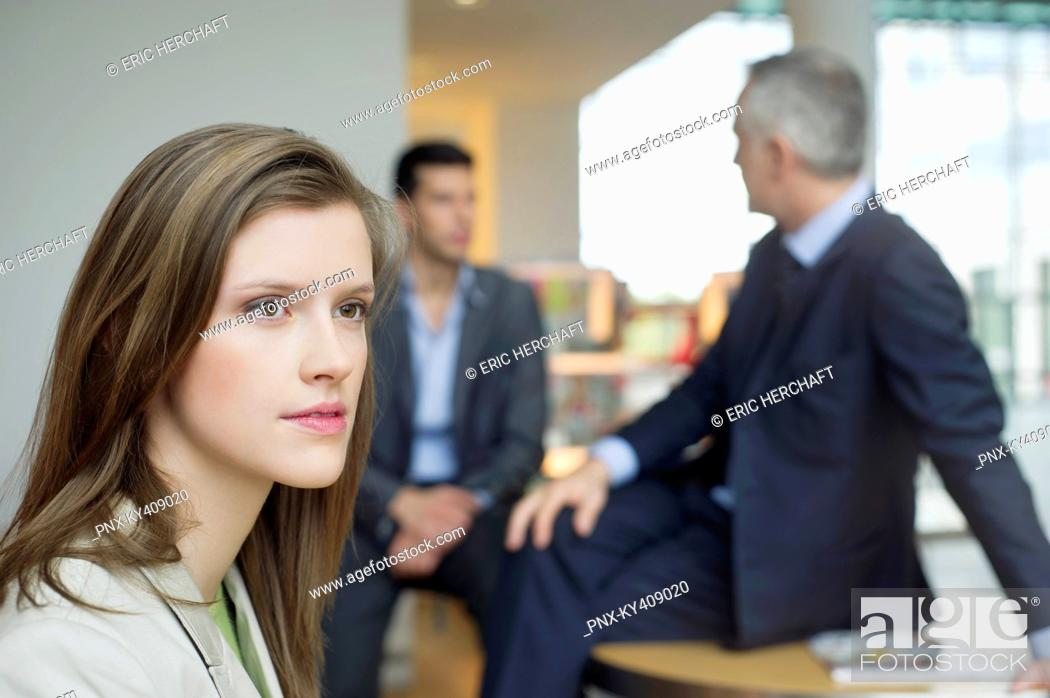 Stock Photo: Female executive thinking in an office with her colleagues discussing in the background.