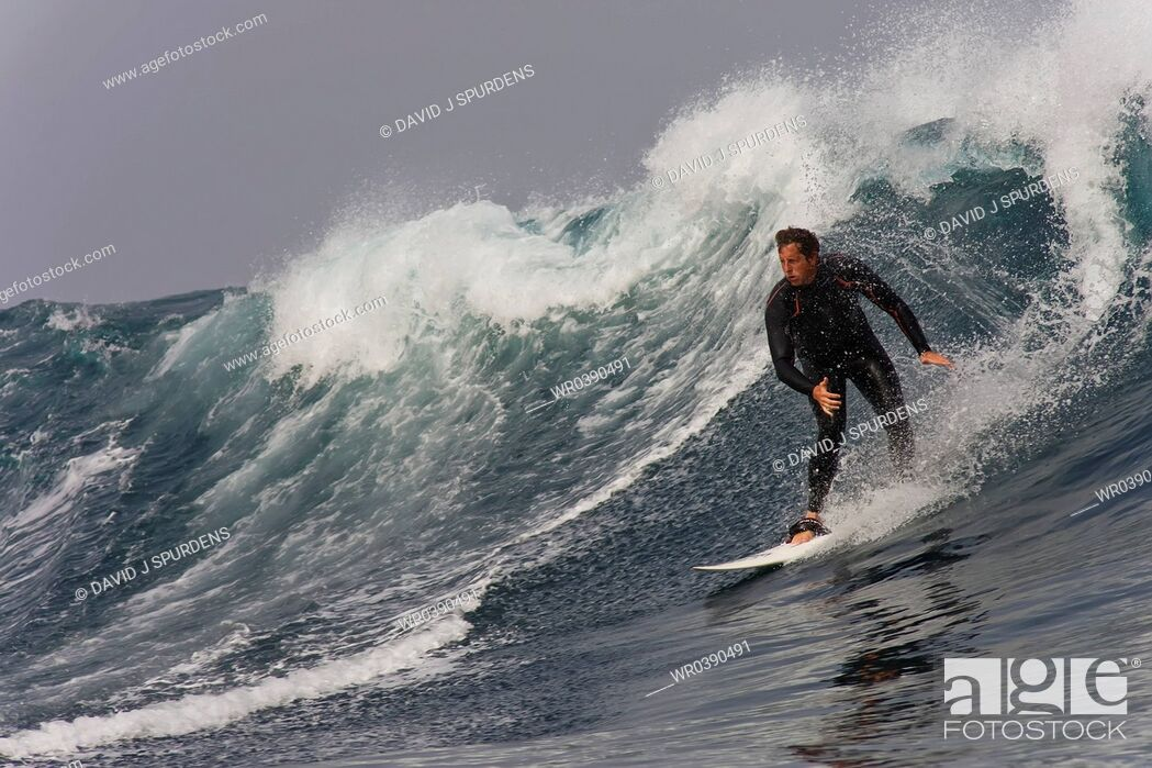 Stock Photo: Middle aged surfer riding a big wave.