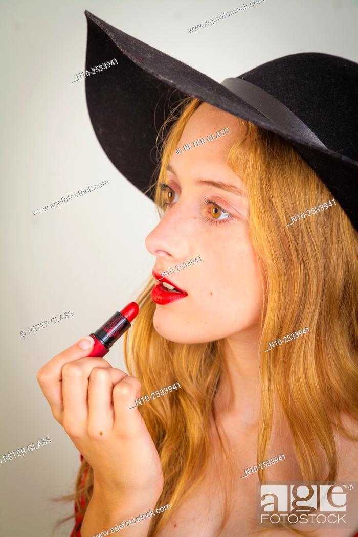 Stock Photo: Blonde teenage girl applying lipstick.