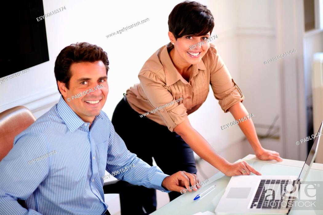 Stock Photo: Portrait of a businessman and businesswoman looking at you while smiling at the office.