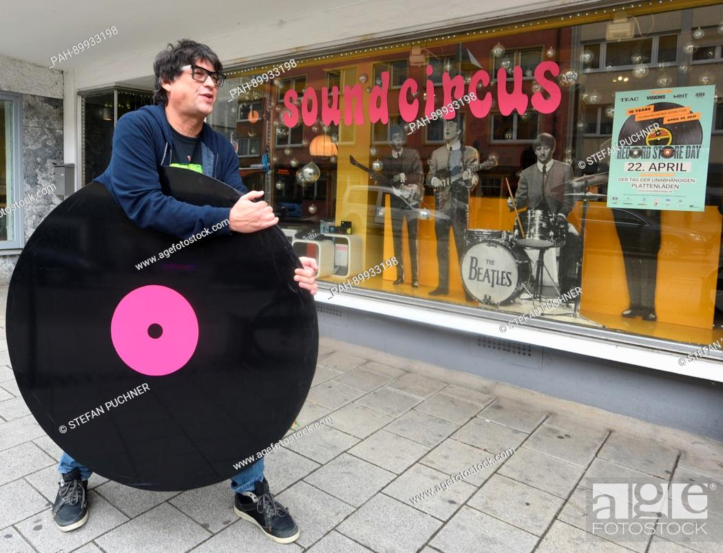 Martin Haag holds an oversized vinyl record in front of his record