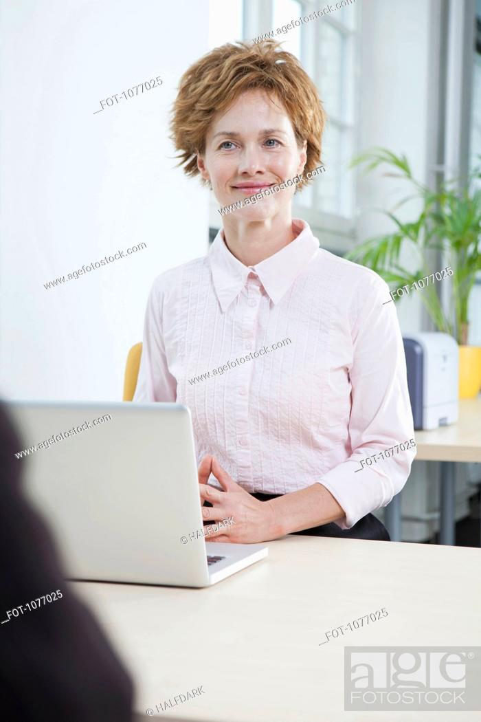 Stock Photo: A businesswoman with a laptop sitting at her office desk.
