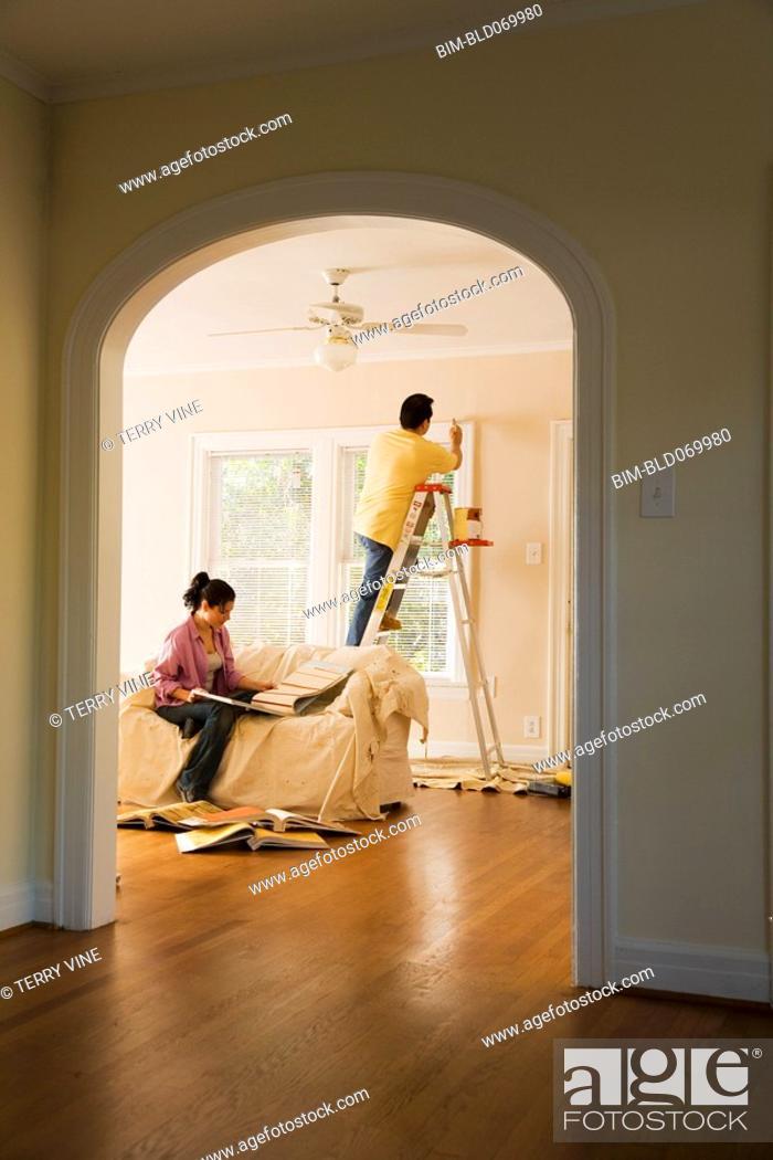 Stock Photo: Hispanic couple painting new home.