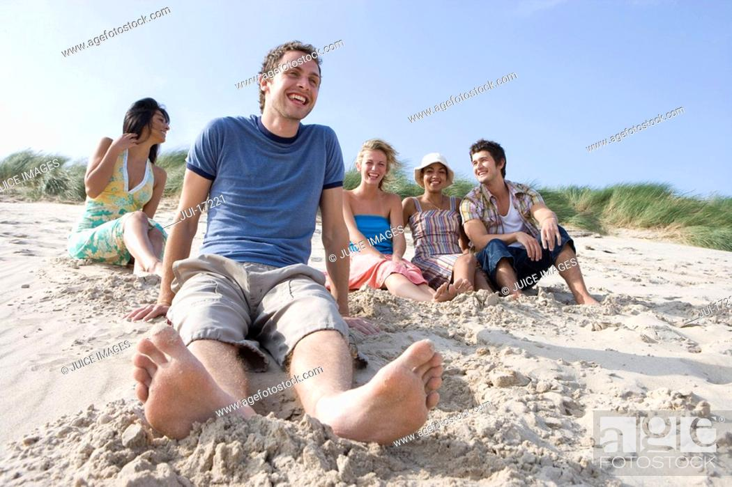 Stock Photo: Portrait of young man sitting at beach, friends in background.