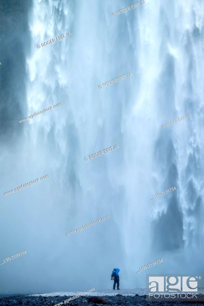 Stock Photo: One of the most powerful waterfalls in Iceland, a classic visiting point for tourists. Here one of them goes too close to the water.