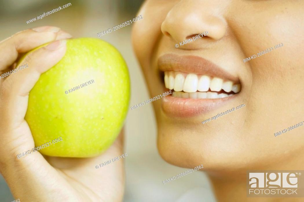 Stock Photo: Close up of woman holding apple next to her mouth.
