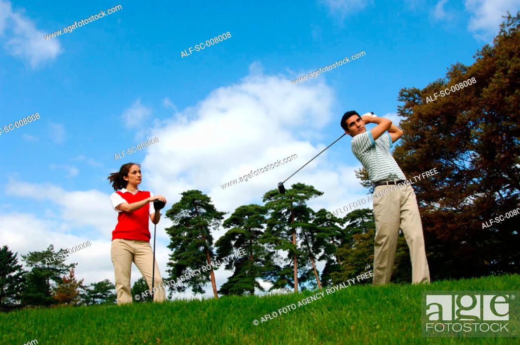 Stock Photo: Man hitting a golf shot with a woman looking on.