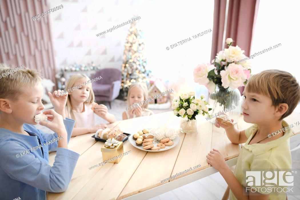 Stock Photo: Four children eating cookies at home.