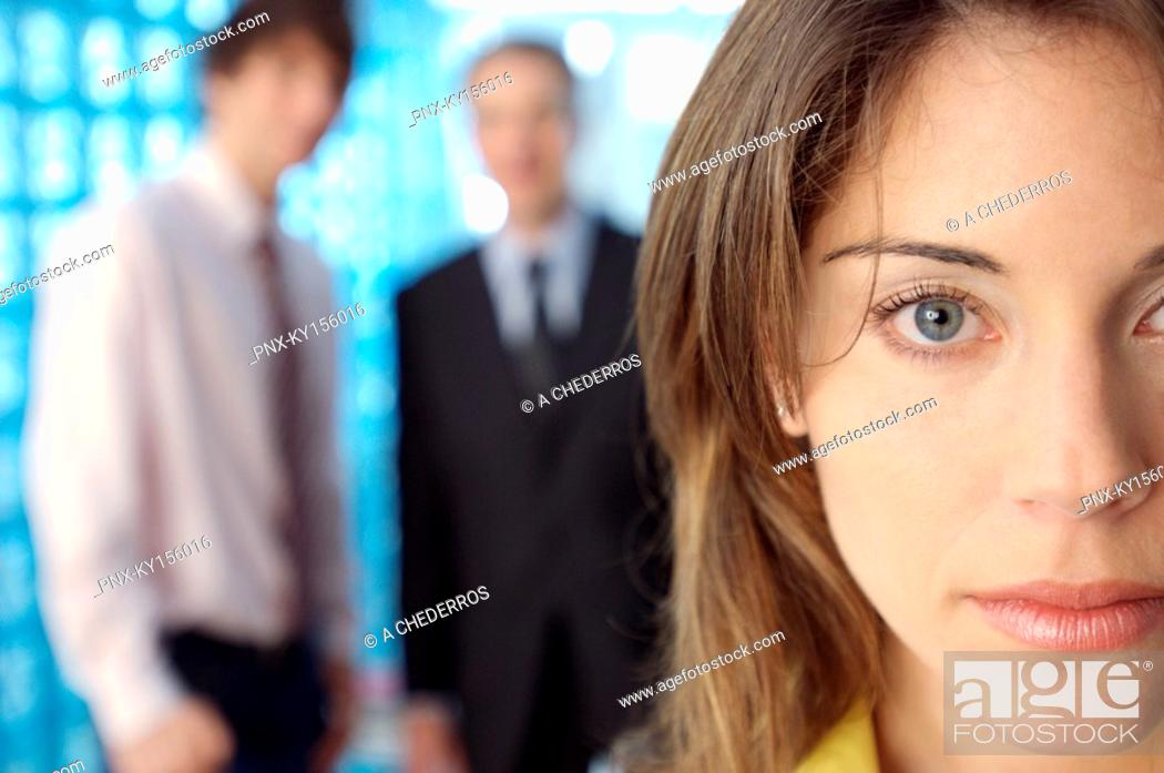 Stock Photo: Businesswoman staring with colleagues in background.